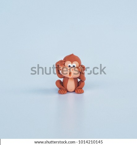 Brown cute cartoon monkey clay with naughty face on white background , plasticine for kid