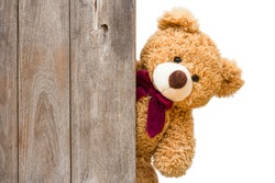 Brown cute teddy bear sneaked behind the old wooden door isolated on white background. Copy space for text and content.
