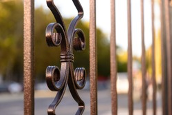 Brown decorative metal fence, angular iron rods and curved upper part. Close-up of the decoration, front view.