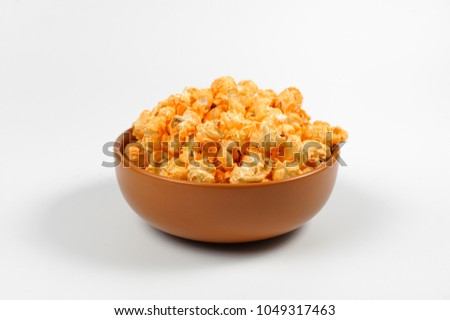 Brown deep plated filled with fresh salty popcorn with a cheese tase isolated on a white background #1049317463
