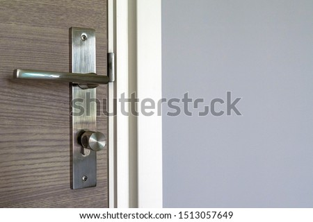 Brown door with stainless steel handles, unlocking the entrance.