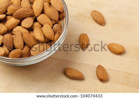 Brown dried almonds on a wood background
