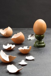 Brown egg on egg stand. Eggshell on table. Black background. Copy space