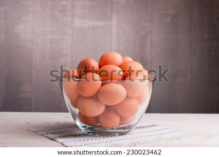 brown eggs in a large glass bowl on a light wooden table and a side view