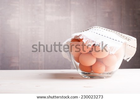 brown eggs in a large glass bowl on a light wooden table side view