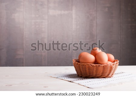 brown eggs in a wicker basket on a light wooden table and a side view