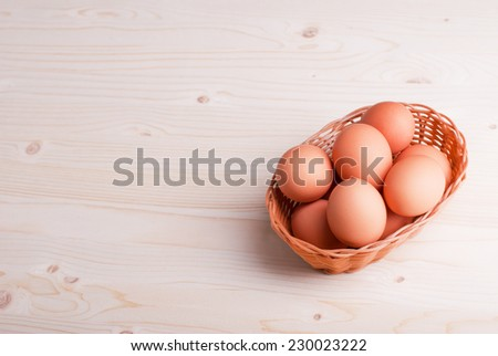 brown eggs in a wicker basket on a light wooden table top view and side view