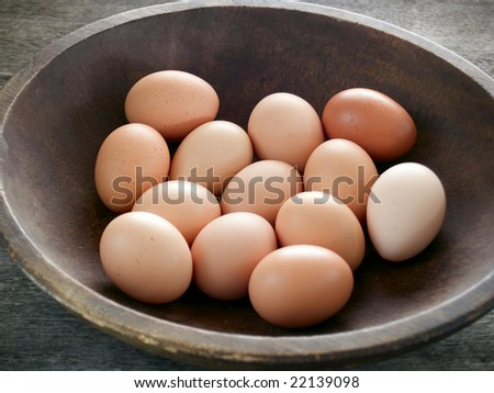 Brown eggs in a wooden bowl on a rustic table - stock photo