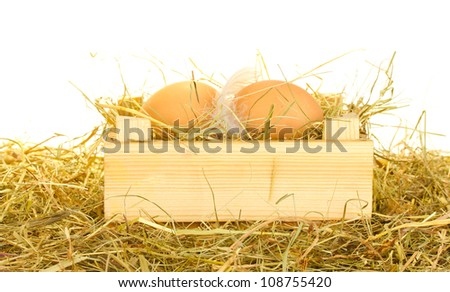brown eggs in a wooden box on hay on white background