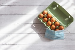Brown eggs in box carton and medical masks on light wooden background. Concept of canceling the Easter holiday during the global pandemic. Flat lay, top view, copy space