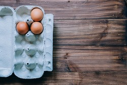 Brown eggs in box on wood table