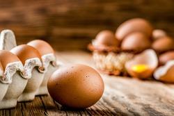 Brown eggs in carton box. Broken egg with yolk in background.