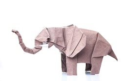 Brown elephant origami figurine. Paper design of animals. Difficult and beautiful art made by child.