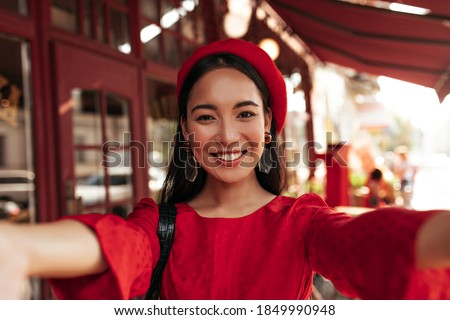 Brown-eyed brunette Asian woman in red dress, bright beret and with stylish earrings smiles widely and takes selfie in street cafe. Сток-фото ©