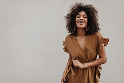 Brown-eyed woman in brown dress smiles on grey background. Stylish brunette curly dark-skinned lady moves on isolated.