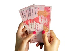 Brown female hands holding multiple Hundred (100) Rupees Pakistani currency bank notes on a white background
