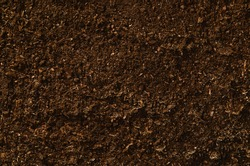 Brown, fertile, sandy soil ready for planting or fertilizing. Camera from above, top view. Natural background for advertisements.