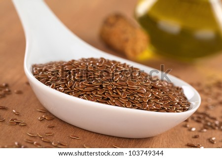 Brown flax seeds on ceramic spoon with linseed oil in the back (Selective Focus, Focus on third into the flax seeds on the spoon)