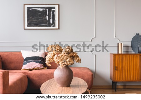 Brown flowers in pottery vase on stylish coffee table in chic living room interior with black and white poster on the grey wall