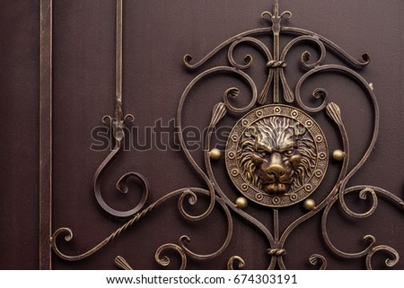 Brown forged decorative grille on the gate close-up with a lion symbol #674303191