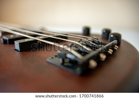 Photo of Brown four string bass guitar bridge picture in shallow depth of field