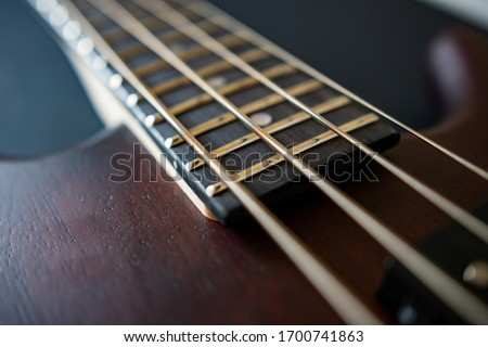 Photo of Brown four string bass guitar picture in shallow depth of field