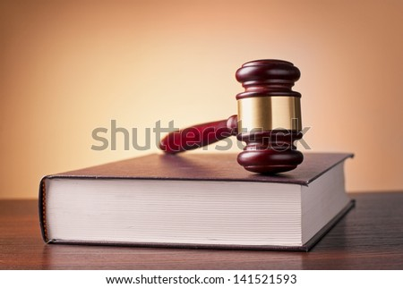 brown gavel and law book on a table on a brown background