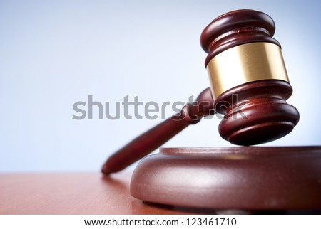 brown gavel with a brass band on a blue background