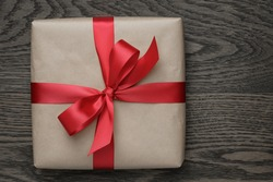brown gift box with red bow on wood table, top view