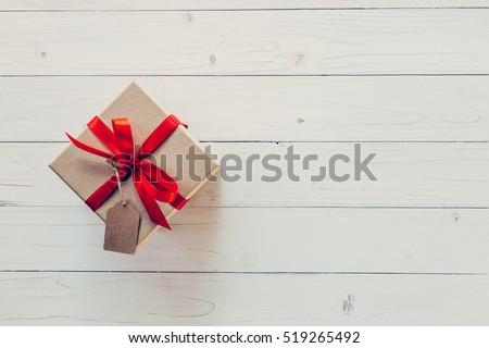 Brown gift box with tag on wooden background. Gift box with red ribbon on wood background with space.