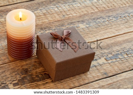 Brown gift or present box and burning candle on old wooden boards. Top view. Holiday concept.