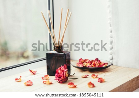 Brown glass bottle container with wood stick diffusers on home wooden window sill with beautiful dry pink rose petals for decoration. Minimalist air freshener concept. Stock foto ©