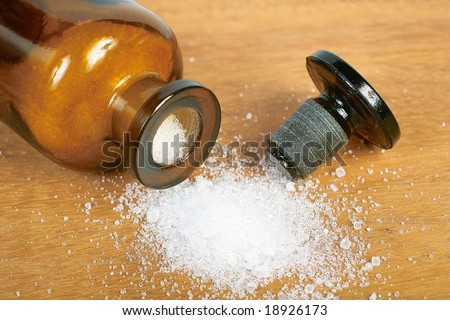 Brown glass bottle with spilled white powder
