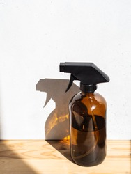 Brown glass spray bottle on wooden shelf on bright background