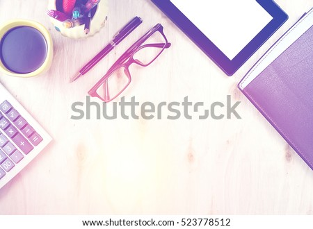 Brown glasses and tablet PC with blank screen, a cup of coffee, finance calculator,  notebook, pen and office supply on wooden background. Office table desk in top view. Vintage cool tone effect