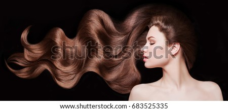 Brown Hair. Beautiful young woman with healthy luxurious long hair on dark background. Hairstyle. Hair cosmetics