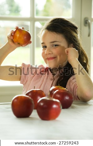 brown haired child presenting an apple. Healthy lifestyle image.