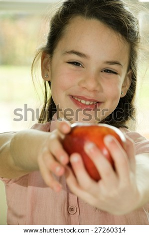 brown haired child presenting an apple.Healthy lifestyle image.