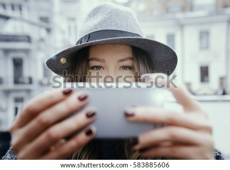 Brown-haired girl in a gray coat and hat, uses mobile flashlight, on a cloudy day, outdoor. . She takes pictures on the phone, holding it with both hands, on the background of houses