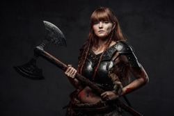 Brown haired grimy amazon from nord holding two handed axe and dressed in dark armour posing in dark background.