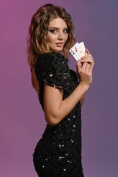 Brown-haired maiden in black dress showing two aces, posing sideways on colorful background. Gambling entertainment, poker, casino. Close-up.