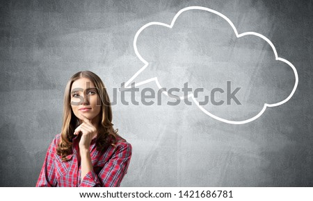 Brown haired woman looks pensive upwards and tries to remember something. Blank speech bubble illustration on grey wall. Puzzled girl has serious facial expression. Woman wears red checkered shirt