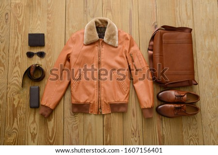 brown handbag, brown leather shoes ,brown leather jacket with sunglasses, purse ,belt on gray background