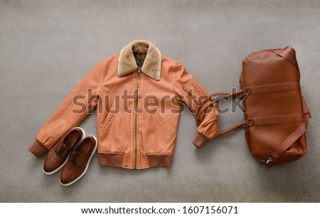 brown handbag, brown shoes ,brown leather jacket on gray background