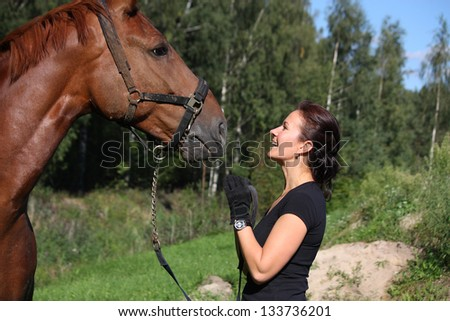 Brown horse and brunette woman portrait in summer