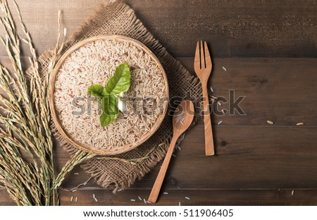 brown Jasmine rice in bamboo basket on dark wood background with copy space, healthy food and diet concept #511906405
