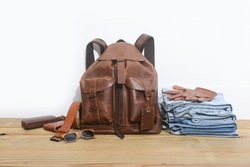 brown leather bag or backpack with brown purse and sunglasses, gloves on stacked blue jeans  on wooden background