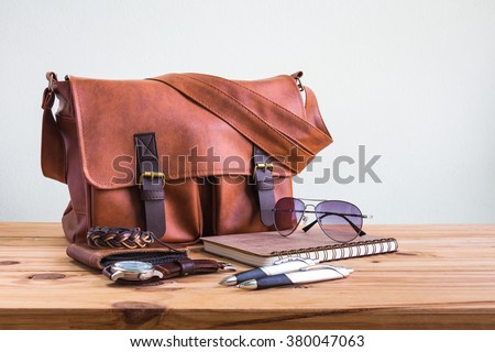 Brown leather bags with men\'s accessories on wooden table over wall background