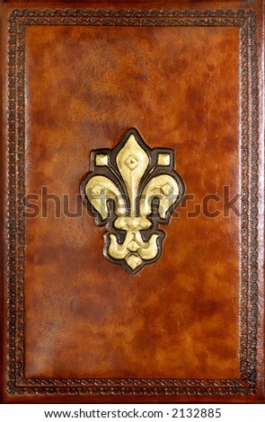 Brown leather book cover with decorative emblem