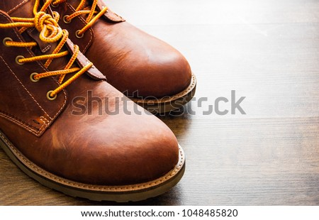 brown leather boots shoes on the brown wooden table background. with copy space. #1048485820